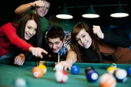 Group of men and women playing pool