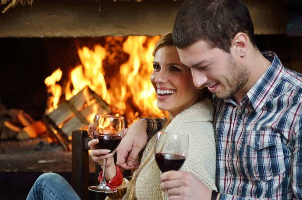 A couple drinking wine in front of a fireplace