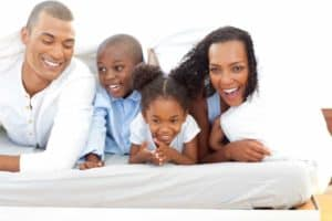 A family laughing in bed.
