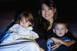 A mother and two children watching a movie together.