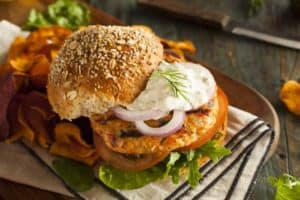 A tasty salmon burger with tartar sauce and onions.