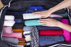 A woman packing clothes in a suitcase.