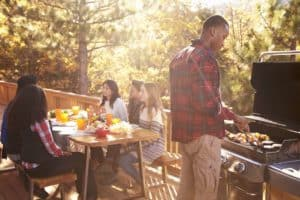 Friends having a cookout on the deck of a cabin.