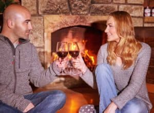 Romantic couple enjoying red wine in front of their cabin's fireplace.